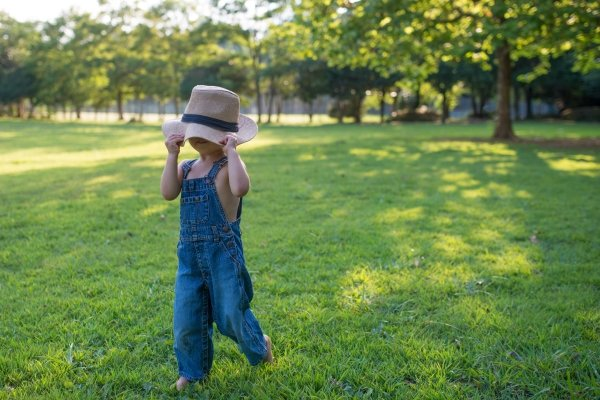 A boy in overalls and a hat walking across a lawn